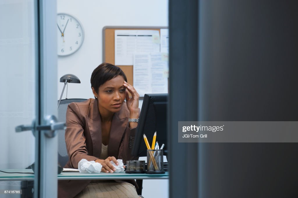 Worried African businesswoman working at computer : Stock Photo