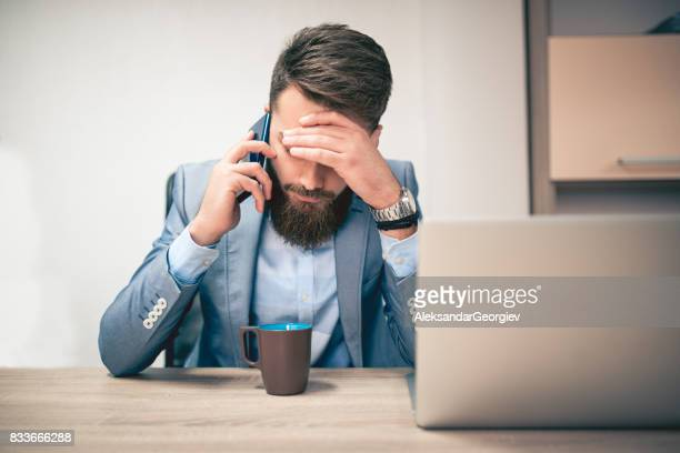 Worried and Exhausted Businessman Talking on Phone in his Office