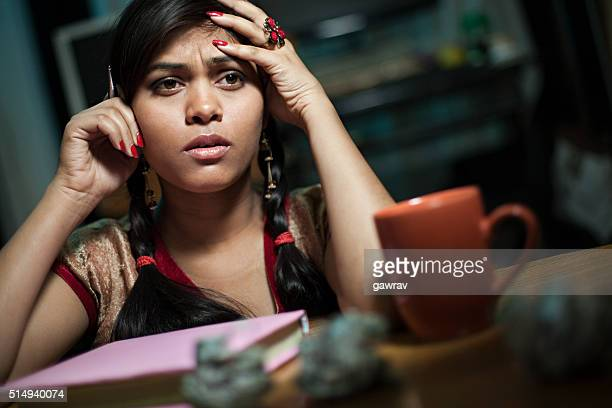Worried and tensed late teen girl holding head and thinking.