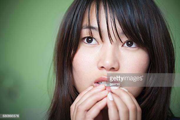 Worried Asian young woman putting her hand on mouth.