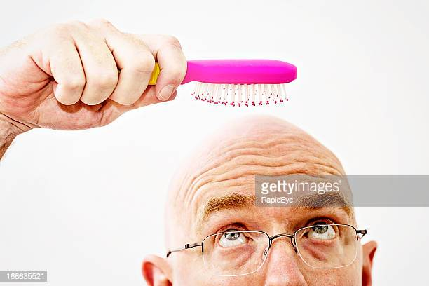 Worried bald man eyes hairbrush: a pointless tool!