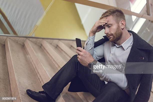 Worried businessman reading a text message on cell phone.