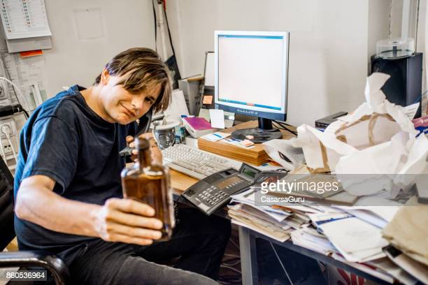 Worried Businessman Sitting At  Desk In Office Drinking Alcohol