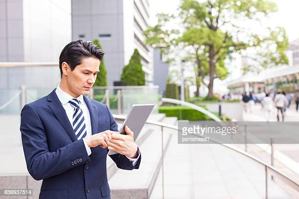 Worried businessman using digital tablet in front of skyscrapers