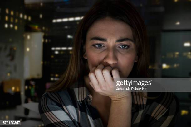 Worried Caucasian businesswoman with hand on chin