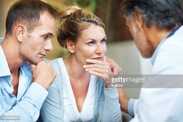 Worried couple in conversation with a doctor