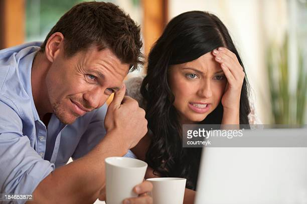 Worried Couple looking at laptop computer
