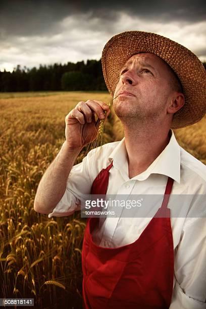 worried farmer looking at storm sky