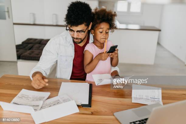 Worried father looking bills while child is sitting in his lap and she is using calculator