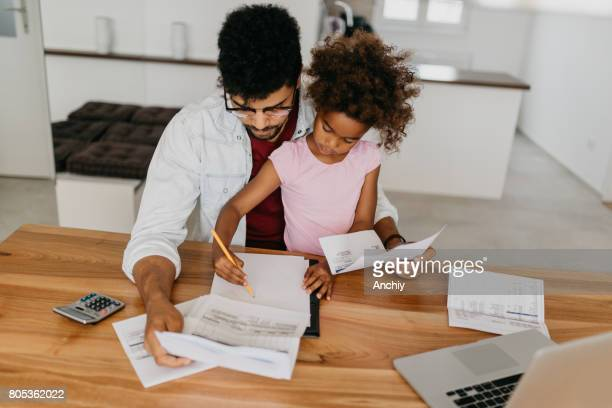Worried father looking the finances with his baby girl
