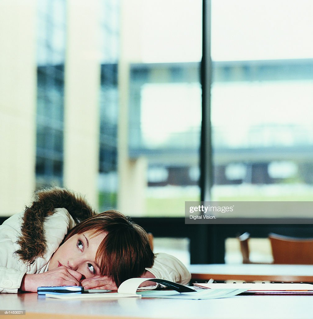 Worried Female University Student With Her Head on a Table Next to a Cheque Book