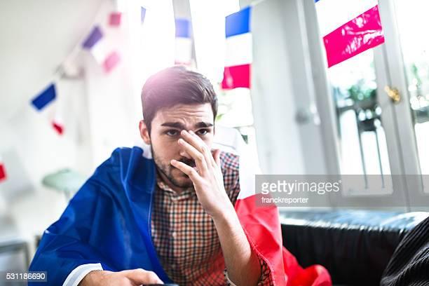 Homme inquiet France supporters comme à la maison en regardant la télévision.