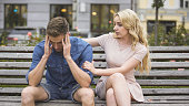 Worried guy sitting on bench, girlfriend calming him down, problems and support