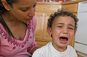 Worried Hispanic mother beside her crying son
