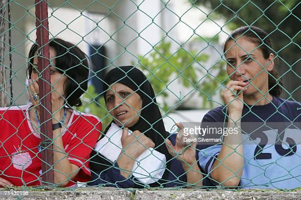 Worried Israeli Arab women look down at the scene where a volley of Hezbollah Katyusha rockets struck July 13 2006 the northern Israeli Arab...