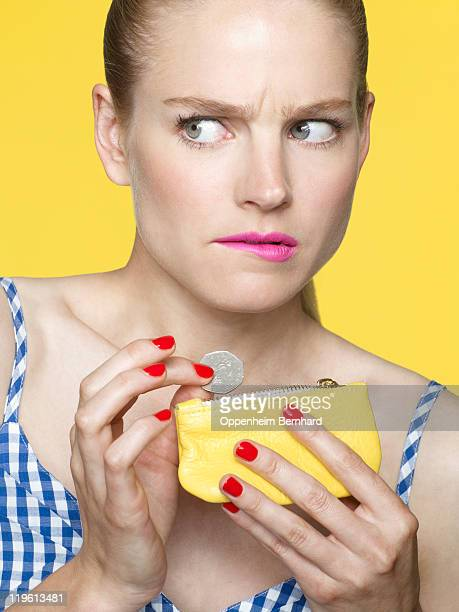 worried looking woman dropping coins in her purse