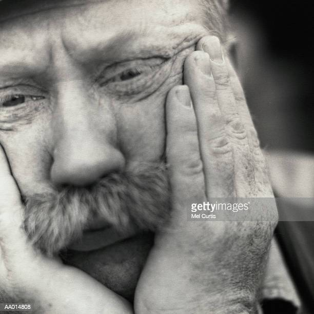 Worried Man Holding His Face in His Hands