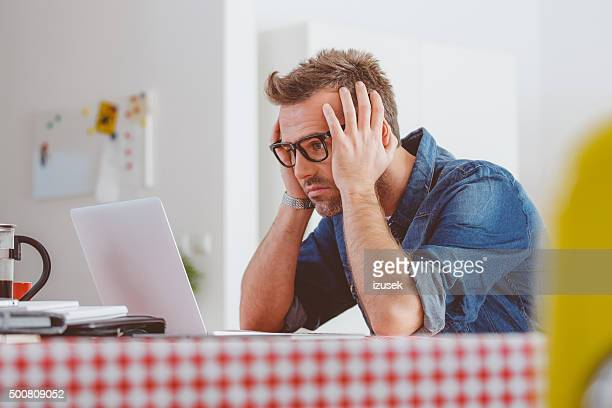Worried man looking at the laptop screen