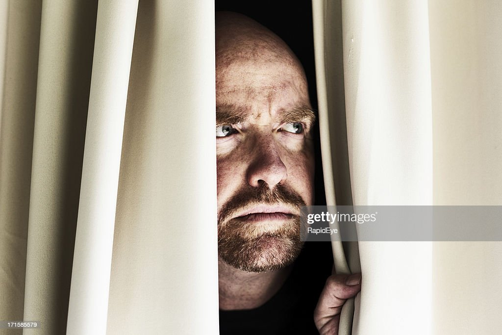 Worried man looks through closed curtains, frowning : Stock Photo