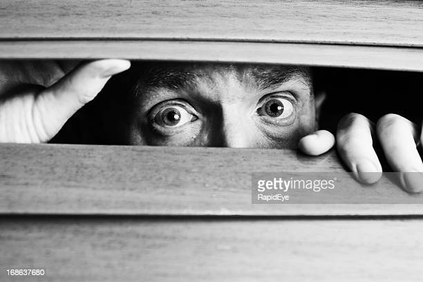 Worried man peeping through wooden venetian blind