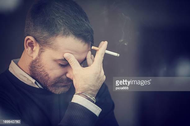 Hombre preocupado fumar un cigarrillo