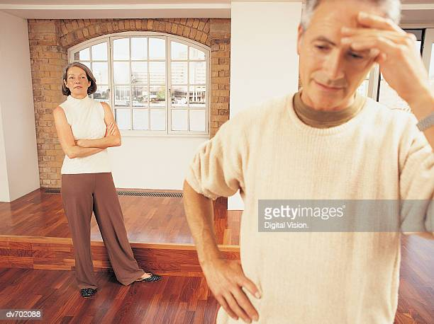 Worried Man Standing in his Apartment with a Woman