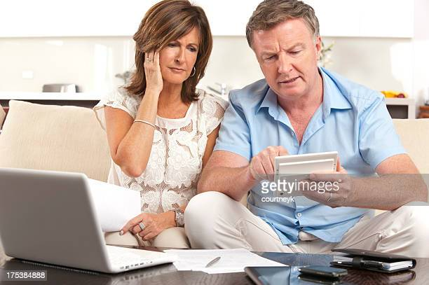 Worried Mature couple doing paperwork with a calculator