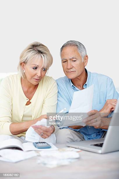 Worried mature couple reading their monthly expenses at home