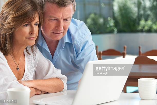 Worried mature couple using wireless technology