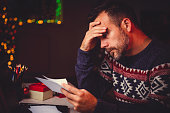 Worried men cheeking his mail late night in home office during christmas holidays