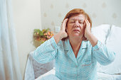 Ill senior woman at home in bed, having headache. Red hair grandmother, living alone, got problem with health.