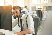 Worried or frustrated business man with headset working on computer in office