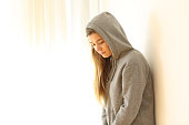 Portrait of a worried pensive teen looking down indoors with a white isolated background at side