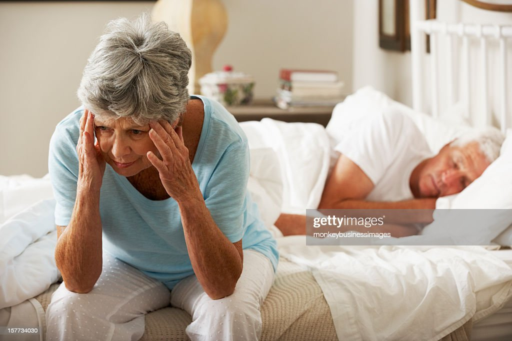 Worried Senior Woman Sits On Bed : Stock Photo