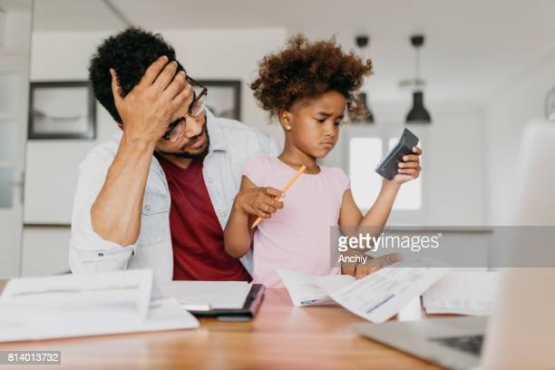 Worried single father doing finances at home with a help of his preschool daughter.