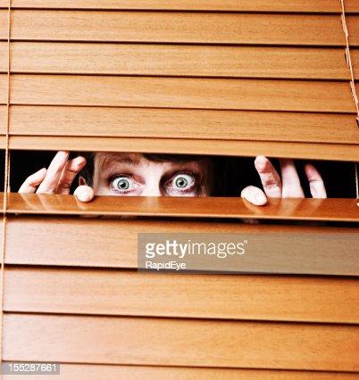 Worried wide-eyed older woman peeps through slats of wooden blind
