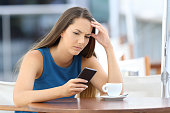 Single worried woman watching a mobile phone and waiting for a call or message sitting in a coffee shop