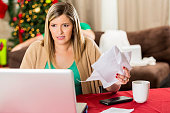 Worried woman holds stack of bills at Christmastime