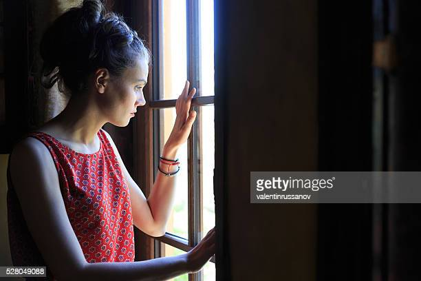 Worried woman looking through the window