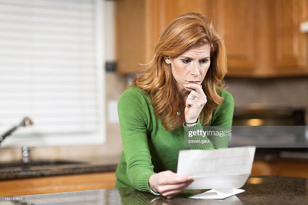 Worried woman reading bank statement