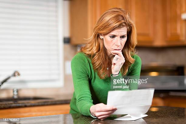 Worried woman reading bank statement