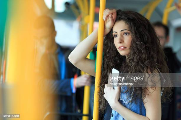 Worried young woman traveling inside of a bus