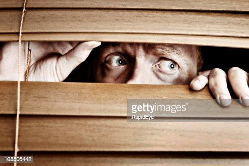 Worried-looking man peeps sideways through venetian blind