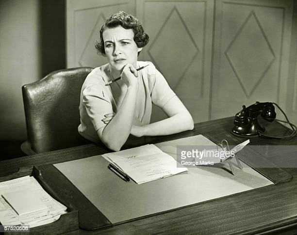 Worrying woman sitting at desk in office, (B&W)