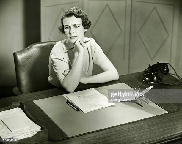 Inquiétant femme assis au bureau en bureau (B & W