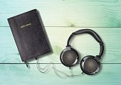 Headphones with Bible in a wooden table.