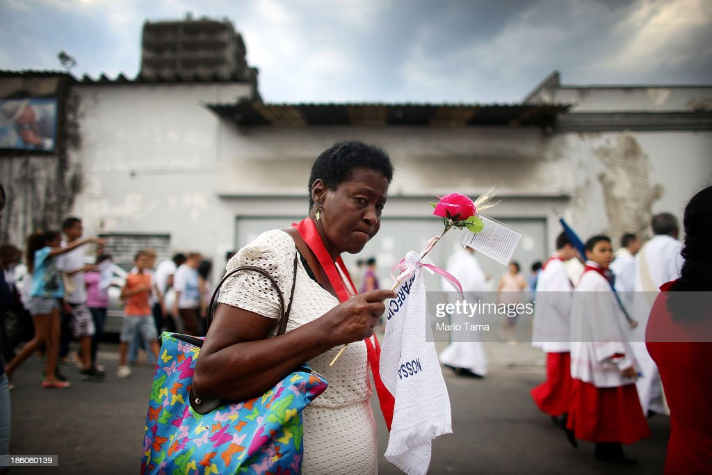 A worshiper carries a flower during a procession near the Nossa Senhora da Penha Church on the final day of the annual October feast of the patron saint marking the 378th anniversary of the church on October 27, 2013 in Rio de Janeiro, Brazil. Pilgrims often climb the entire 382 steps that lead to the church, originally constructed in 1635, which is perched on a rocky hill. Brazil holds more Catholics than any other country.