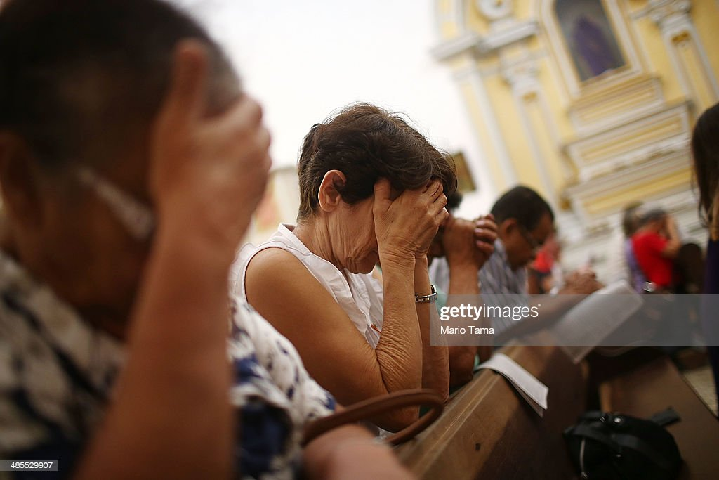 Worshipers bow their heads during services in the Igreja Matriz da Nossa Senhora dos Remedios church during Semana Santa (Holy Week) festivities on April 18, 2014 in Paraty, Brazil. Holy Week marks the last week of Lent and the beginning of Easter celebrations for Catholics. Brazil holds more Catholics than any other country. Paraty was built as a Portuguese colonial town shortly after Portugal colonized Brazil in 1500. Paraty flourished during the 18th Century as the main port to ship Brazilian gold to Portugal.