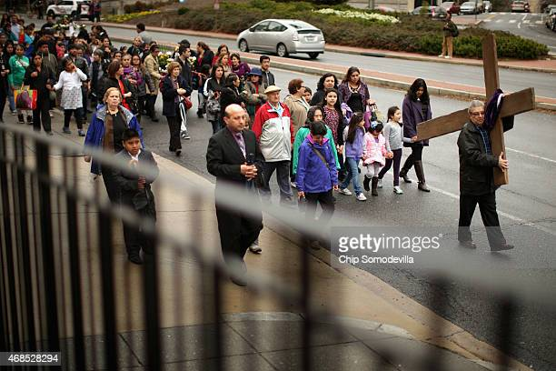 Worshipers carry wood crosses and religious statues during the Via Crusis or 'Way of the Cross' to mark Good Friday April 3 2015 in Washington DC...