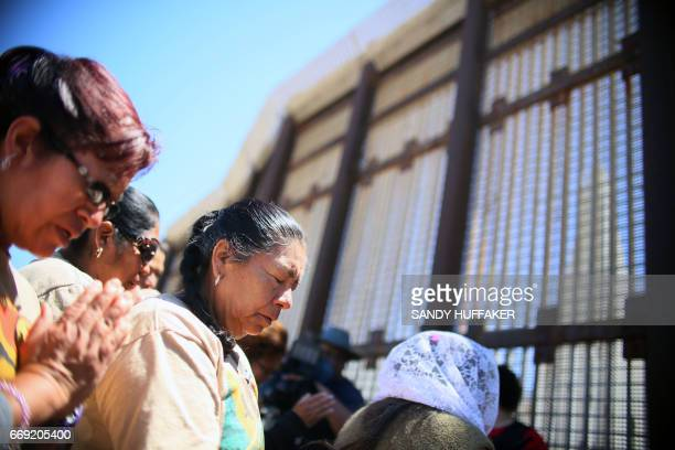 Worshipers engage in a binational Easter mass along the USMexico border fence at Friendship Park in San Ysidro California on Sunday April 16 2017 /...